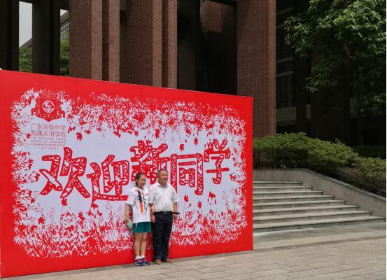 家长与新生入学纪念,校方的欢迎背景墙喜庆而温馨